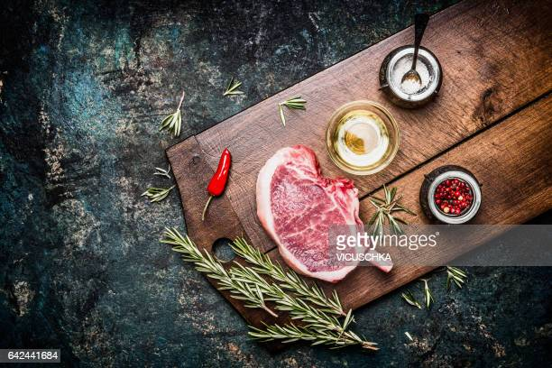 Raw Porco Iberico meat ribs cutlet with oil and spices on cutting board, top view