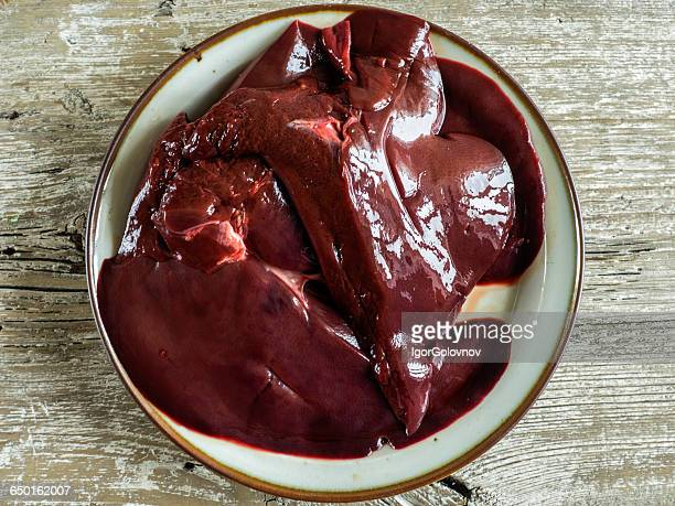 raw pork liver on a plate - animal internal organ stock photos and pictures