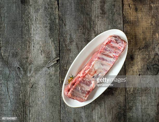 Raw pork ribs on a plate on wooden table