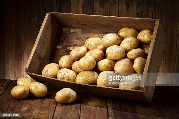 Raw potatoes in a crate on rustic wood table
