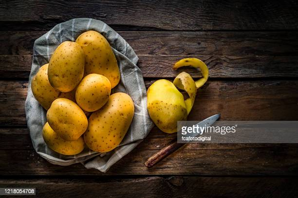 raw potatoes on rustic wooden table. copy space - raw potato stock pictures, royalty-free photos & images