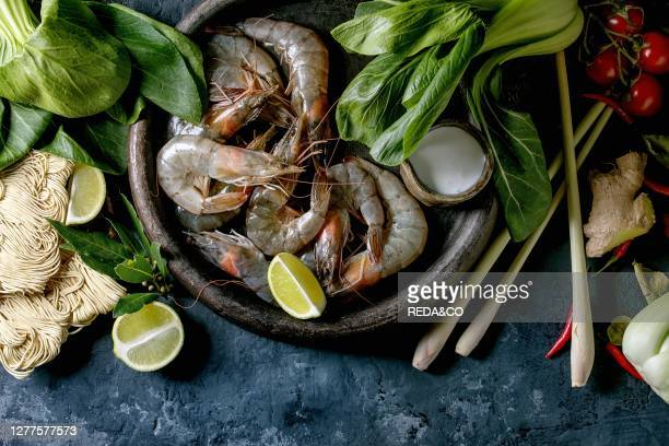 Raw prawns shrimp with asian noodles. Cocnut milk and vegetables. Ingredients for cooking asian dinner or thai soup tom yum. Dark concrete...