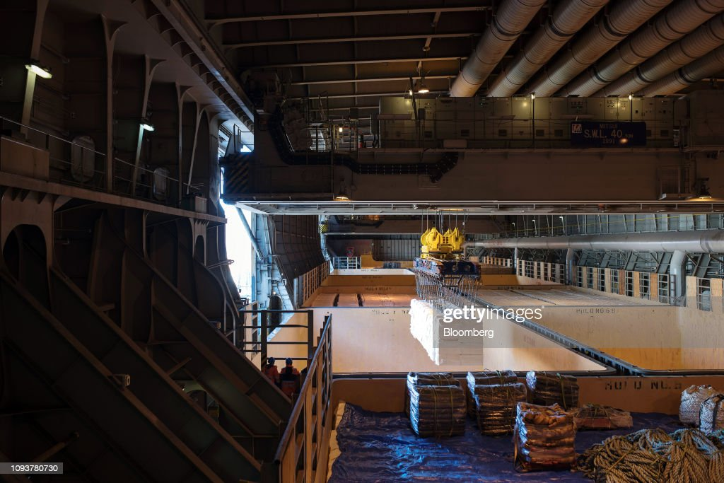 Raw pulp is loaded into the hold of a ship moored at the