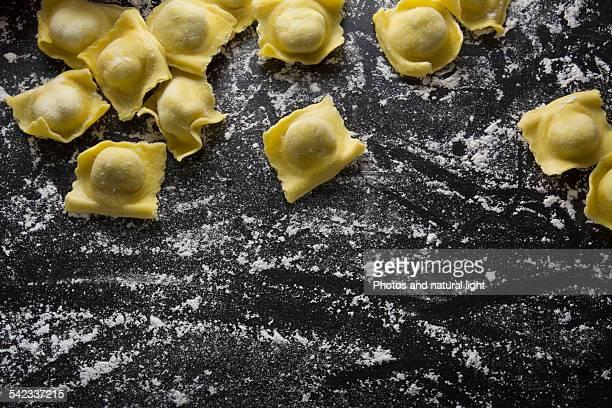 Raw ravioli on black background