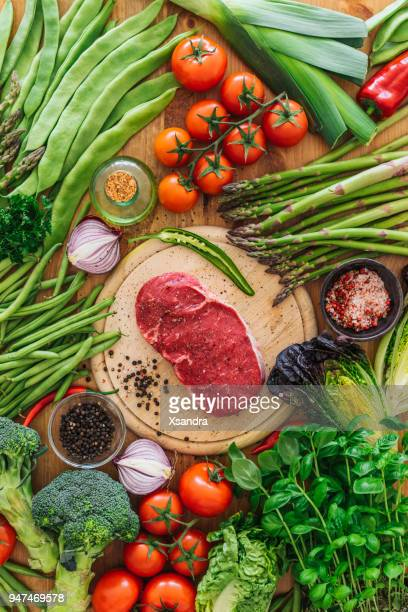Raw rib eye steak with vegetables