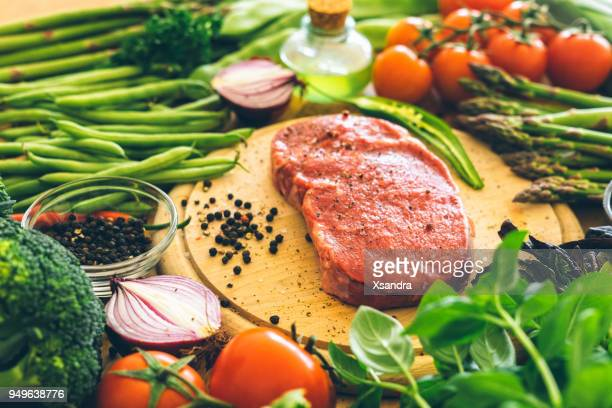 raw rib eye steak with vegetables - low carb diet stock photos and pictures