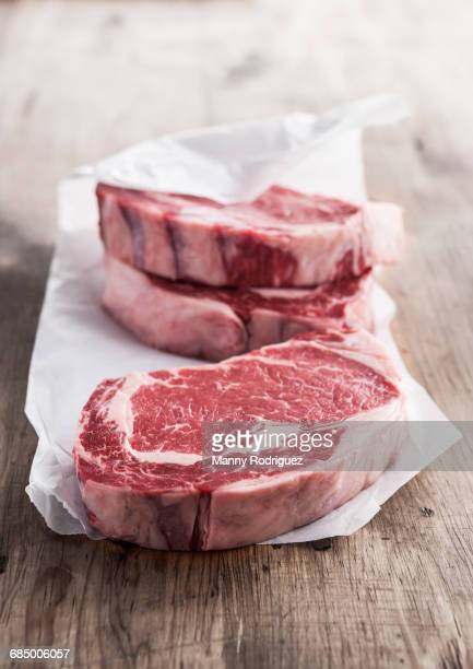 Raw rib eye steaks on butcher paper