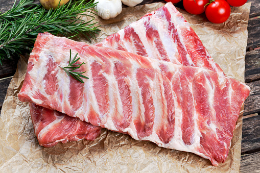 Raw ribs with a rosemary and vegetables. on crumpled paper 508695276