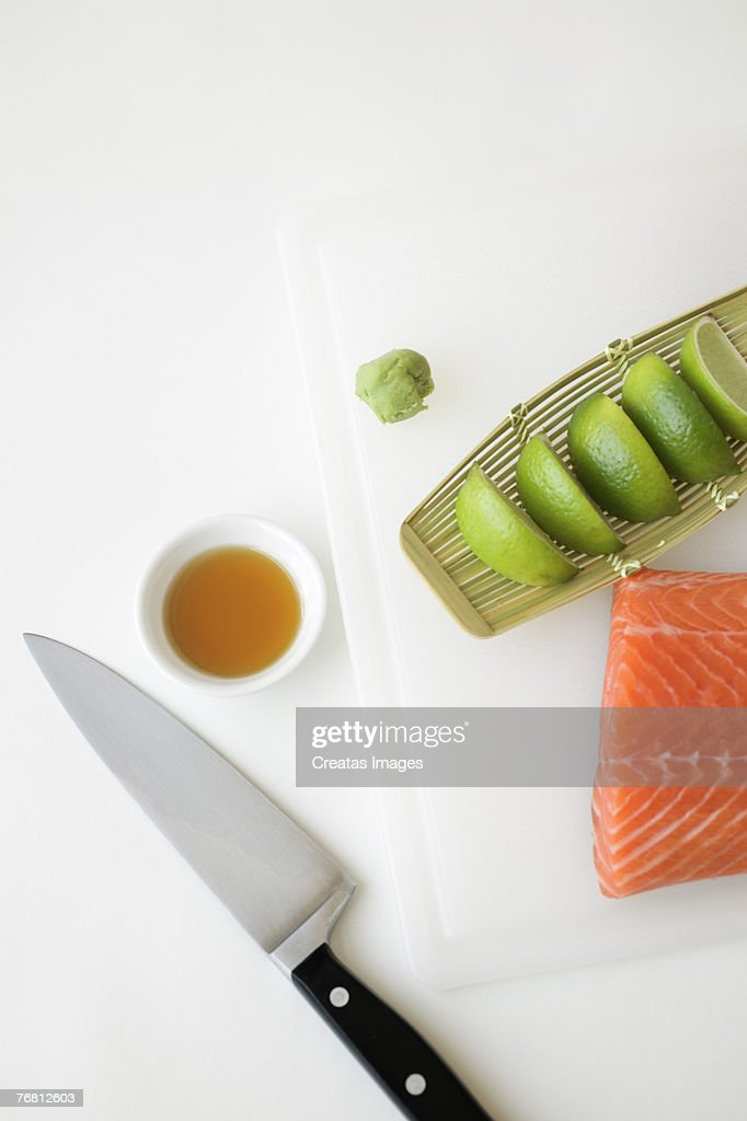 Raw salmon and limes with knife and sauce : Stock Photo