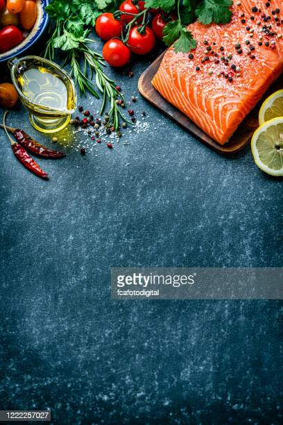 bordo filetto di salmone crudo su sfondo scuro. spazio di copia - salmone frutto di mare foto e immagini stock