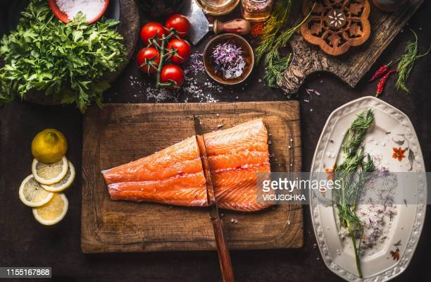 raw salmon half fish fillet on cutting board with knife and flavor ingredients - chopping board stock pictures, royalty-free photos & images
