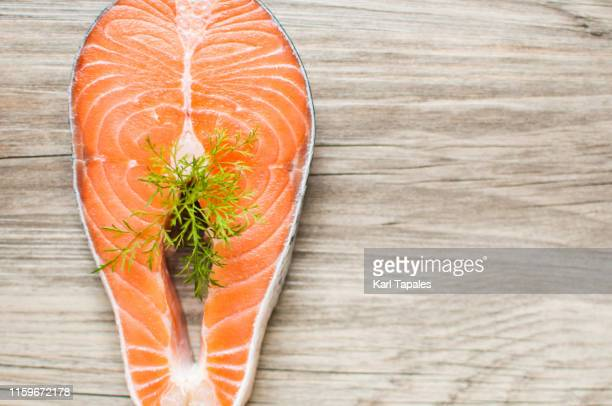 raw salmon steak garnished with dill on a wooden table - schaamhaar stockfoto's en -beelden