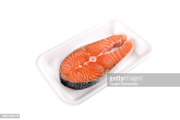 Raw salmon steak in tray isolated on white background