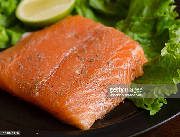 Raw salmon steak marinated in plate garnish with a lettuce leaf and a wedge of lime