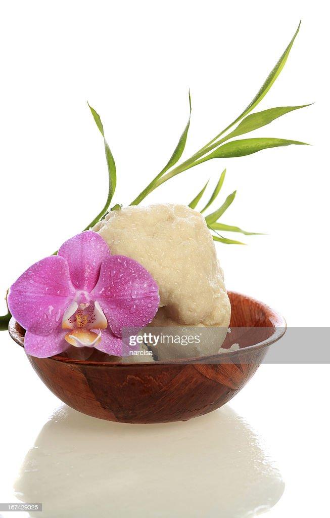 Bruto a manteiga de karité em Tigela de madeira com Orquídea e Bambu : Foto de stock