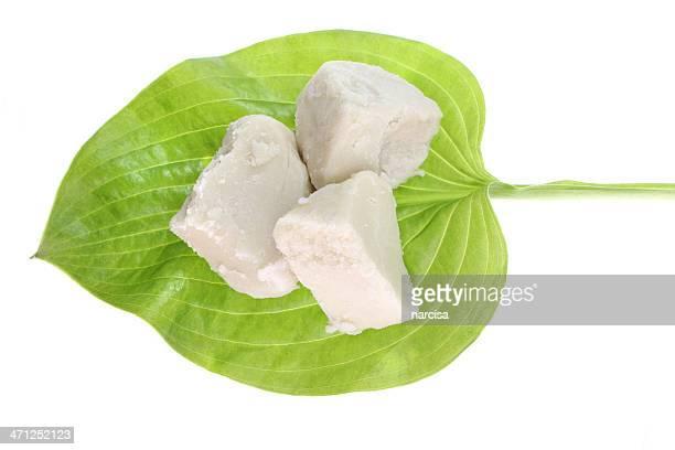 Raw shea butter on green leaf