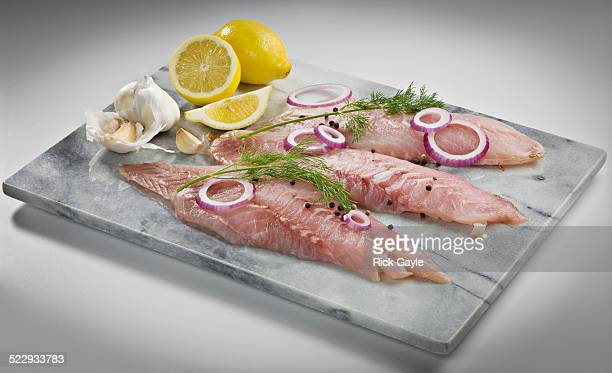 Raw snapper on marble cutting board with lemon and herbs