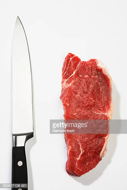 Raw steak and knife, overhead view