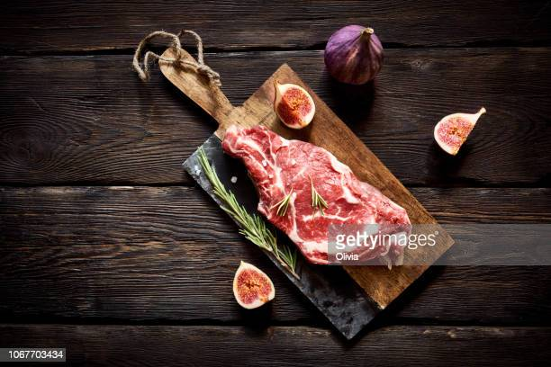 raw steak on cutting board ready to cook - raw food stock pictures, royalty-free photos & images
