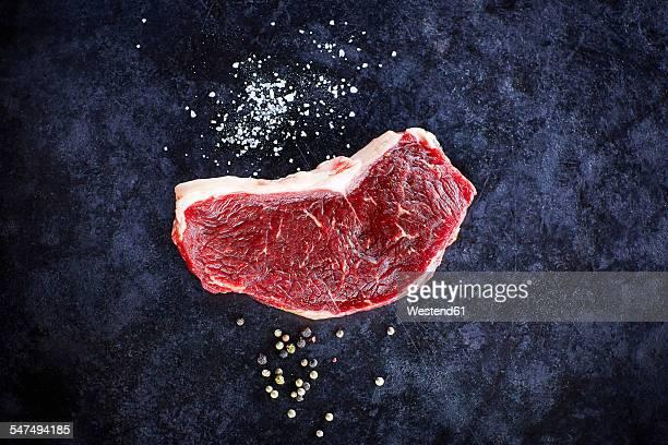 Raw striploin steak and salt