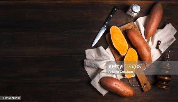 raw sweet potato on wooden cooking board - sweet potato stock pictures, royalty-free photos & images