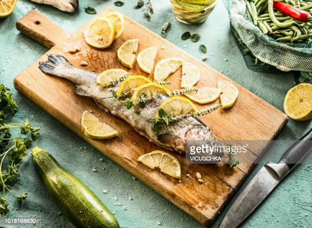 raw trout fish on cutting board stuffed with herbs and lemon slices - food stock-fotos und bilder