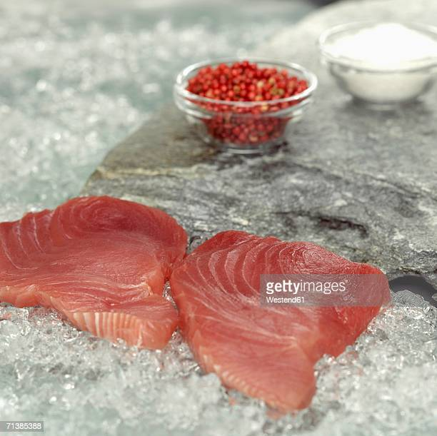 Raw tuna steaks on crushed ice, close-up