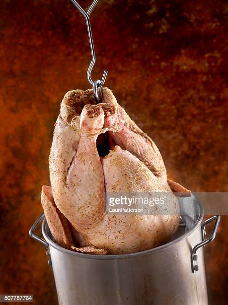 raw turkey going into the deep fryer - breaded stock photos and pictures