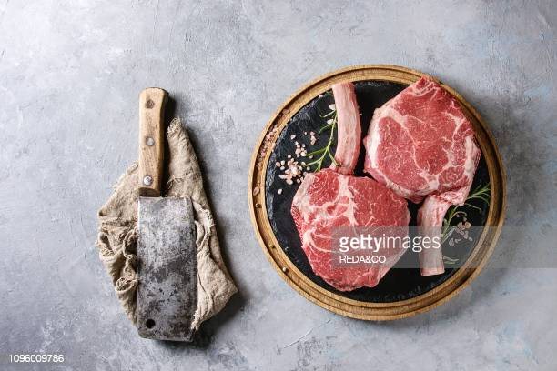 Raw uncooked black angus beef tomahawk steaks on bones served with salt, pepper, vintage butcher cleaver on round wooden slate cutting board over...