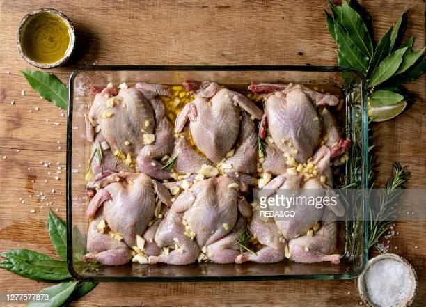 Raw uncooked quails butterfly in marinade in glass baking tray with lime. Salt. Pepper. Olive oil. Garlic and greens over wooden cutting board. Flat...