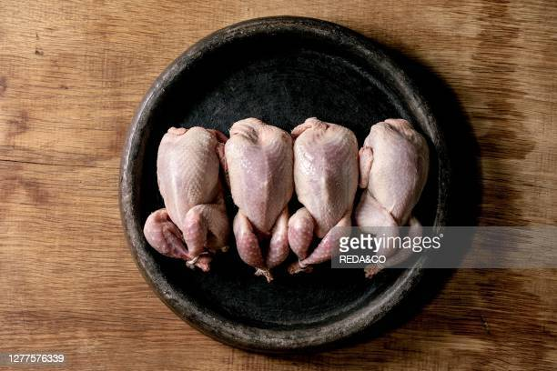 Raw uncooked quails ready for marinat in clay tray over wooden background. Top view. Space.