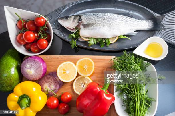 raw uncooked sea bass with  lemon, olive oil, herbs and spices - mediterranean sea stock pictures, royalty-free photos & images