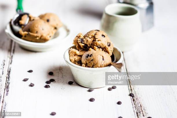 raw vegan chocolate chip cookie dough made from almond meal, coconut flour, coconut oil, chocolate chips and maple syrup - dough stock pictures, royalty-free photos & images