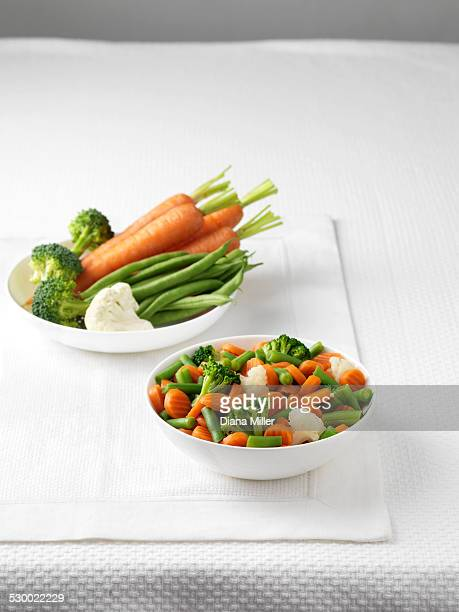 raw vegetables in bowl with bowl of boiled vegetables - boiled stock pictures, royalty-free photos & images