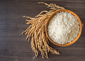 raw white rice (Thai Jasmine rice)  in brown bowl and and ear of rice or unmilled rice on wooden background