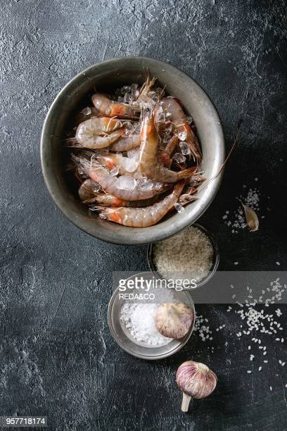 Raw whole fresh uncooked prawns shrimps on ice on vintage metal tray with cooking ingredients above Sea salt rice garlic over black texture...