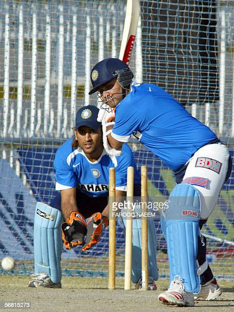 Indian cricketer Virender Sehwag plays a shot as wicketkeeper Mahendra Dhoni looks on during a practice session at the Pindi Cricket stadium in...