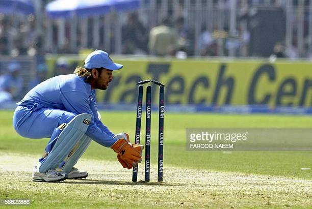 Indian wicketkeeper Mahendra Dhoni breaks the wicket as he successfully runs out Pakistani batsman Shoaib Malik during the second One Day...