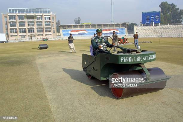 Pakistan Cricket Board groundstaff member Mohammad Bashir sits on a roller as he prepares the wicket for the fourth One Day International cricket...