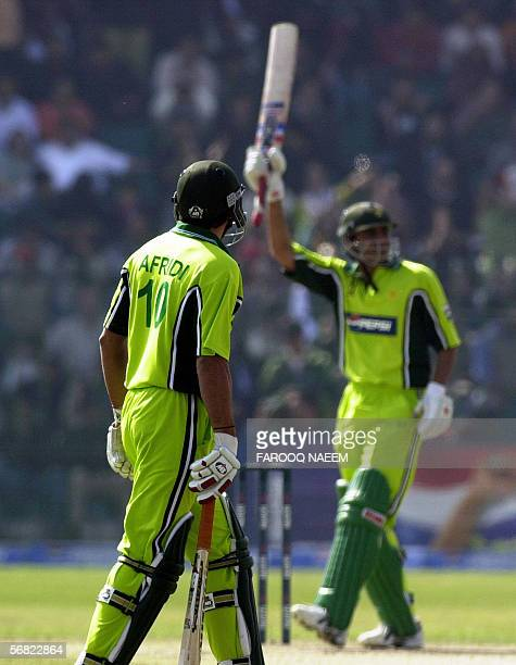 Pakistani cricketer Shahid Afridi watches as teammate Younis Khan celebrates scoring his halfcentury during the second One Day International match...
