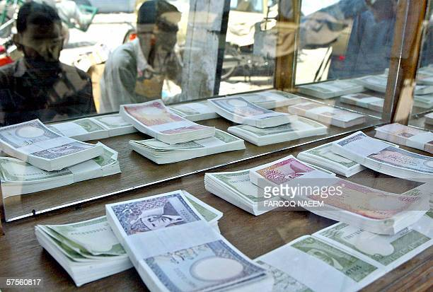 Pakistani men look at currency at a shop in Rawalpindi 09 May 2006 Pakistan's liquid foreign reserve continuing an upward movement at last crossed...