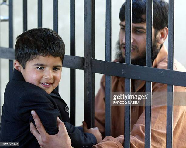 Pakistani prisoner Zulfiqar facing murder charges reaches through the bars of his cell to greet a child relative at Adyala Jail in Rawalpindi 26...