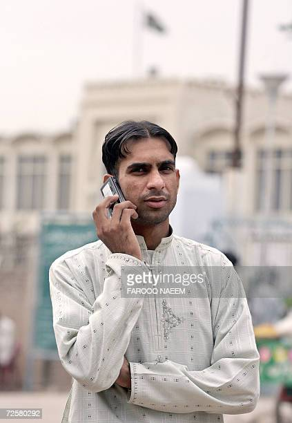 Saeed Hussain cousin of jailed British national Mirza Tahir Hussain talks on his cellphone as he waits outside the Adiala Jail to see Mirza in...