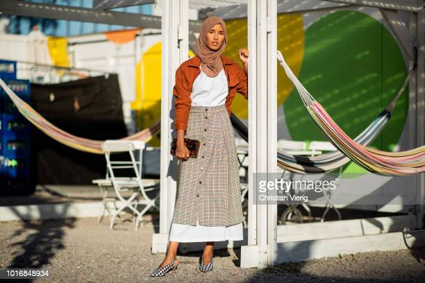 Rawdah wearing checked skirt white dress orange jacket clutch is seen outside Iben during Oslo Runway SS19 on August 14 2018 in Oslo Norway