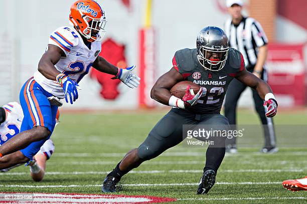 Rawleigh Williams III of the Arkansas Razorback runs the ball and is pursued by Marcus Maye of the Florida Gators at Razorback Stadium on November 5...