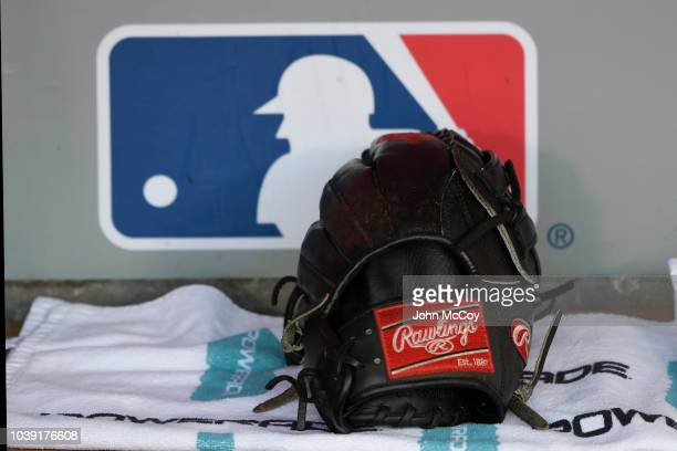 Rawlings baseball glove sits in the Seattle Mariners dugout in front of an MLB logo before a game with the Los Angeles Angels of Anaheim at Angel...