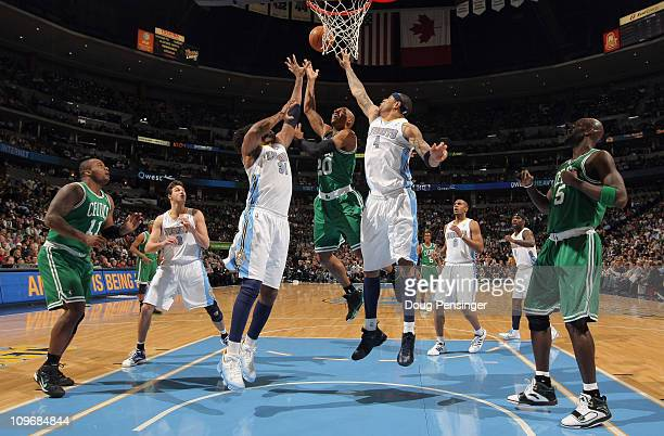 Ray Allen of the Boston Celtics puts up a shot against Nene and Kenyon Martin of the Denver Nuggets during NBA action at the Pepsi Center on February...