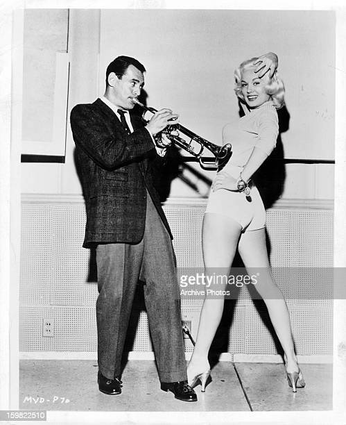 Ray Anthony playing trumpet next to a posing Mamie Van Doren in publicity portrait for the film 'The Second Greatest Sex' 1955