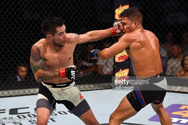 Ray Borg punches Geane Herrera in their flyweight bout during the UFC Fight Night event at Bridgestone Arena on August 8, 2015 in Nashville,...