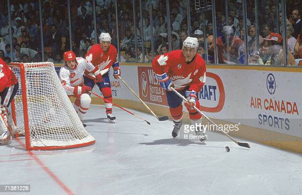 Ray Bourque controls the puck as he is chased by a Soviet opponent while Canadian Larry Murphy follows them behind the goal during Game 2 of the 1987...